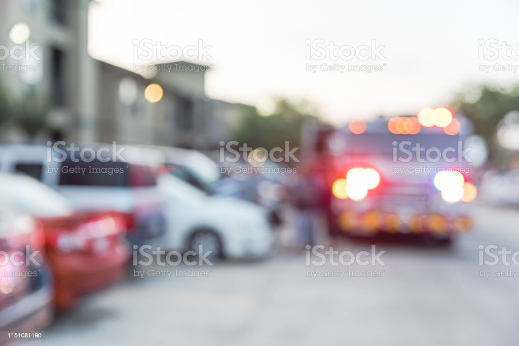 Blurred image fire trucks, firemen and resident at apartment fire in...