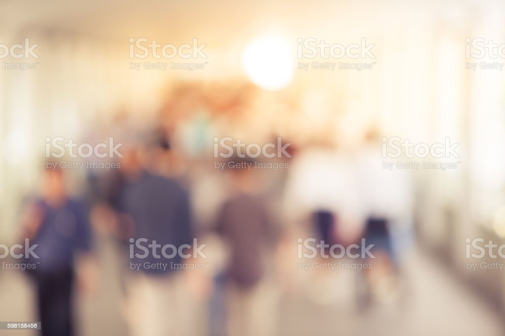 Abstract blurry background of many people walking on skywalk in the...
