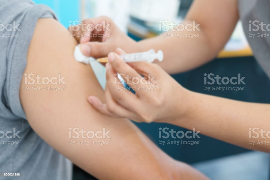 Blurry Background of Nurse are vaccinations to patient. To prevent diseases that are prevalent. closed-up of hand with vaccine shot. stock photo