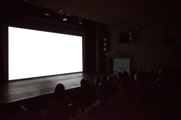 blurry background of people watching movie in the movie theater with white screen. - projection screen stock photos and pictures