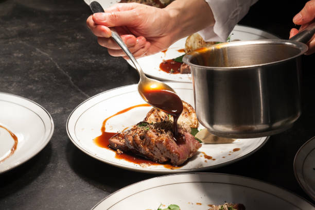Blurry background of the chef is pouring the sauce on beef is main dish. Blurry background of the chef is pouring the sauce on beef is main dish. gourmet stock pictures, royalty-free photos & images