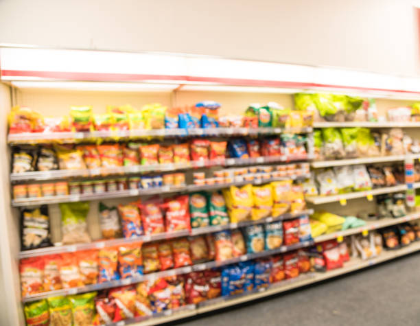 Blurry background snacks and canned chips at pharmacy store in America Blurred image of snacks and canned chips aisle in store at Humble, Texas, US. Wide perspective view shelves variety of snacks, defocused blurry background bokeh light in supermarket. Business concept. snack aisle stock pictures, royalty-free photos & images