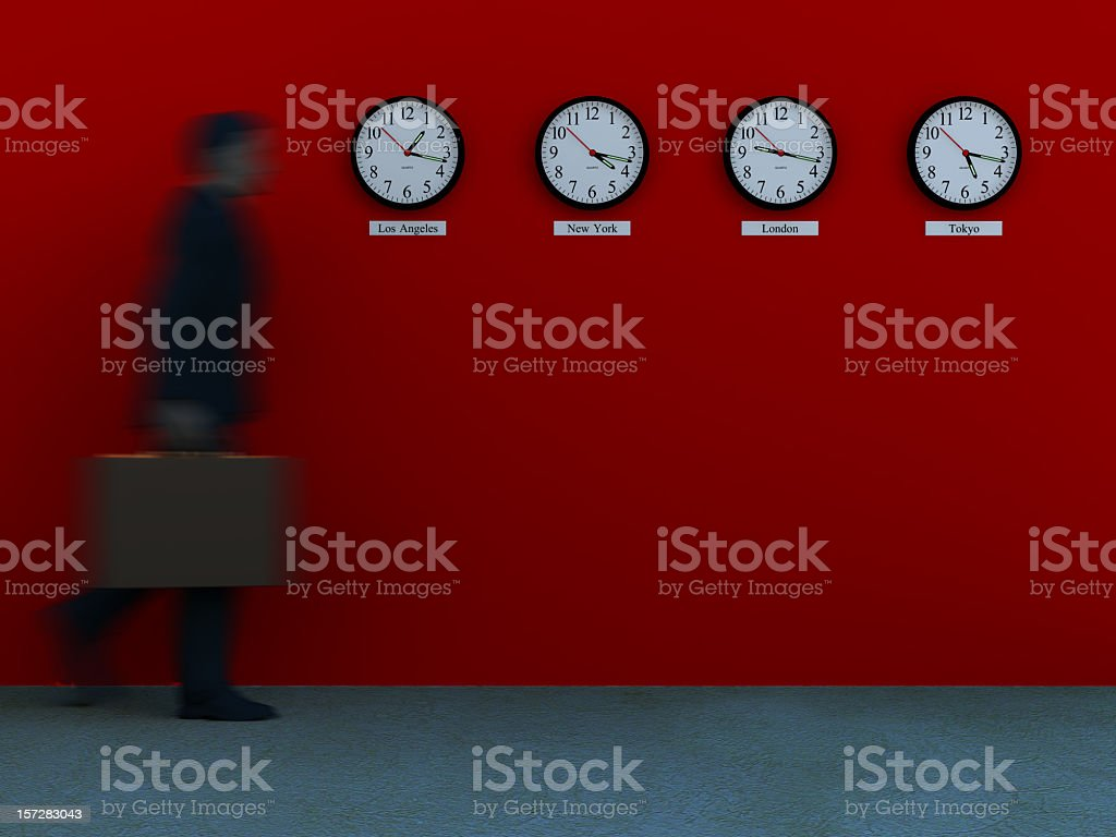 A blurry businessman walking toward four clocks stock photo