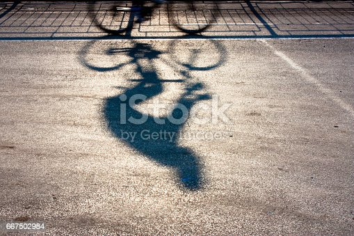 istock Blurry cyclist silhouette and shadow 667502984