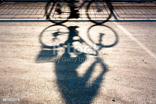 812812808 istock photo Blurry cyclist silhouette and shadow 667503278