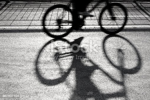 812812808 istock photo Blurry cyclist silhouette and shadow 667507104