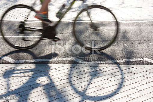 812812808 istock photo Blurry cyclist silhouette and shadow 803311660