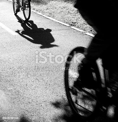 812812808 istock photo Blurry  cyclists silhouettes and shadows 694839144