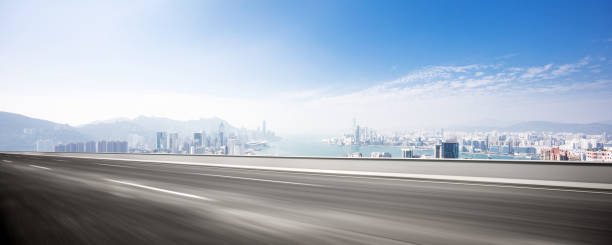 blurry empty asphalt road with modern cityscape stock photo