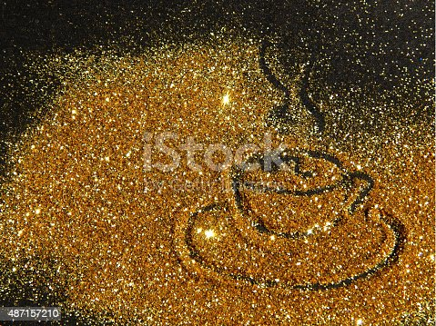 Blurry golden cup of coffee of glitter sparkle on black background