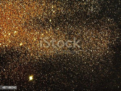 Blurry golden glitter sparkle on black background