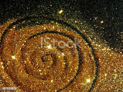 Blurry golden spiral of glitter sparkle on black background like a star galaxy