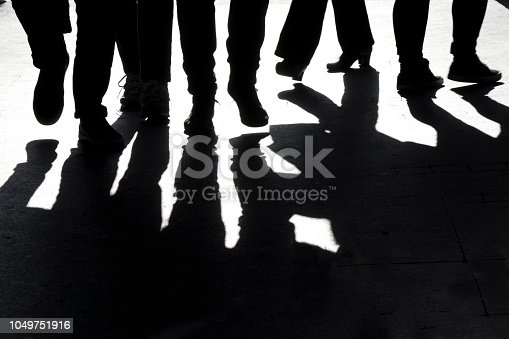 istock Blurry high contrast silhouettes and shadows of legs 1049751916