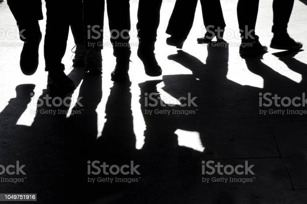 Photo of Blurry high contrast silhouettes and shadows of legs