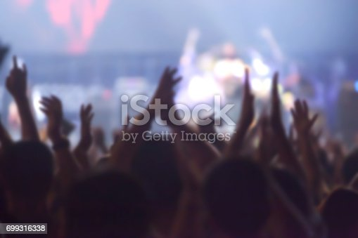 istock blurry image background of many audience concert in big rock concert. 699316338