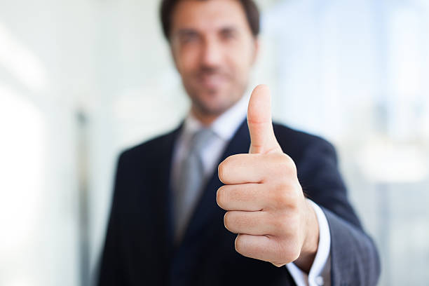 A blurry image of a businessman giving a clear thumbs up stock photo