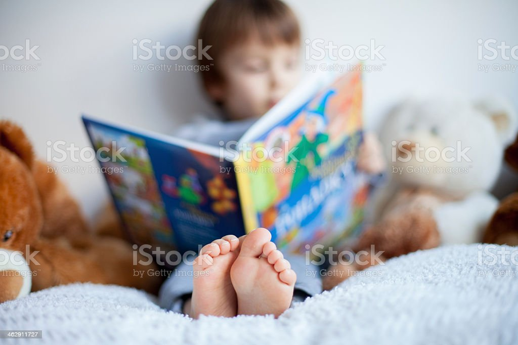 A blurry image of a young boy reading a book by himself stock photo