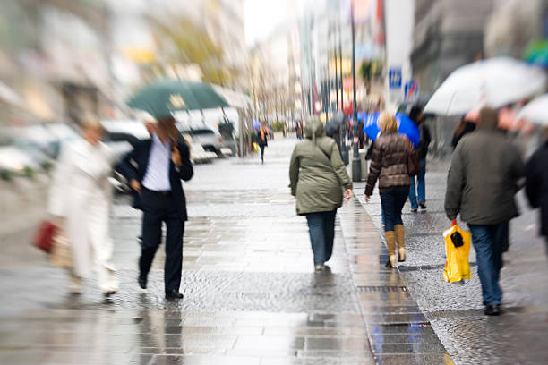blurry image of people walking on the pavement in the rain - yt stock pictures, royalty-free photos & images
