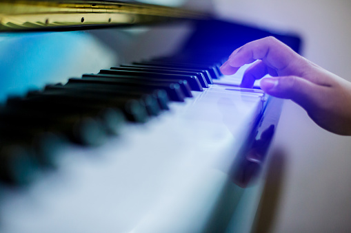Blurry image of piano key with hand kid press it to play music.