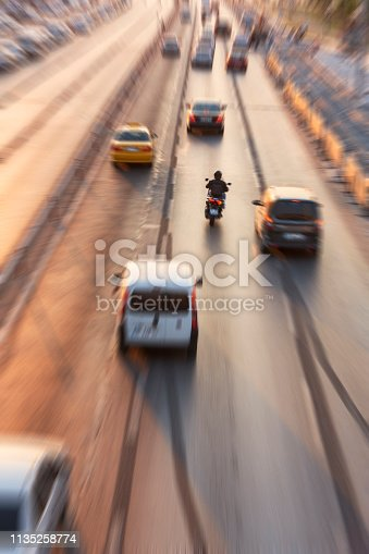 Blurry image of rush hour traffic on busy highway at sunset. Car traffic on street at sunset time.