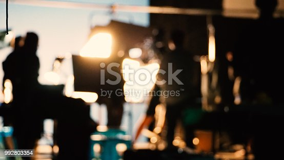 istock Blurry images of silhouette people film crew team working behind the scenes 992803354