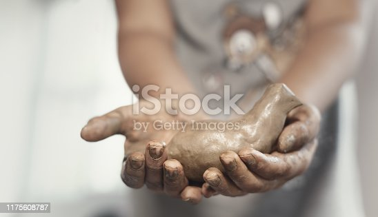 157287453 istock photo Blurry little girl showing her art work (a bird,dove ) from clay.Child creative activities. 1175608787