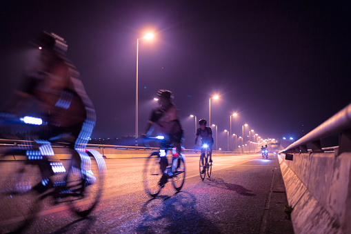 Blurry of Cyclists ride through lighted city