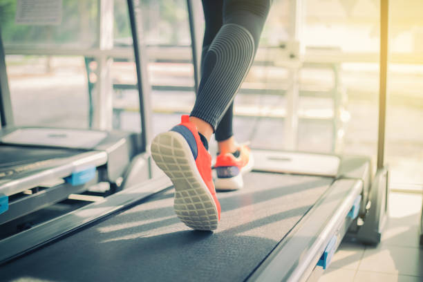 blurry of  running sport shoes at the gym while a young caucasian woman is having jogging on the treadmill - carpet runner stock photos and pictures