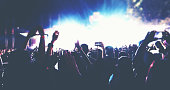 Blurry of silhouettes of concert crowd at Rear view of festival crowd raising their hands on bright stage lights