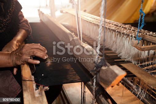 Blurry old Asian woman working with weaving loom. Household weaving - use for weaving traditional Thai silk. Selective focus and color toned.
