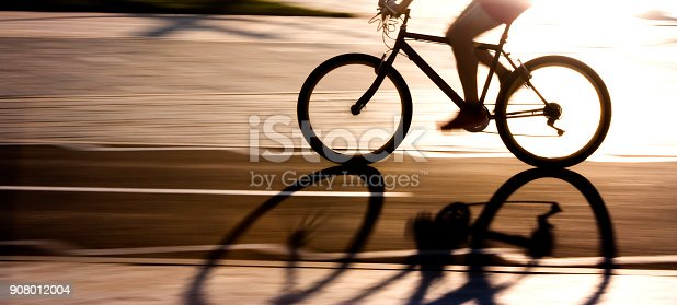 istock Blurry panning silhouette and shadow of a cyclist 908012004