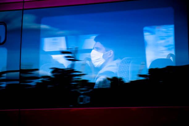 Blurry person wearing face surgical mask riding on a window seat of a public, with reflections