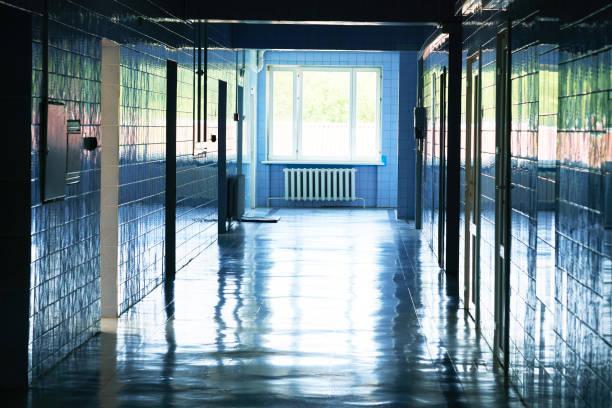 Verschwommenes Foto von Krankenhaus-Spaziergang mit hellblauer Beleuchtung. Weißer Boden mit kühler Tonfarbe mit Lichttunnel in der Bildmitte. – Foto