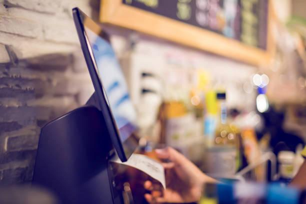 verschwommenes bild der kassiererin druckt quittung mit registrierkasse im café oder geschäft. verkäuferin erhält zahlung von kunden in café oder geschäft. - kassenbon stock-fotos und bilder