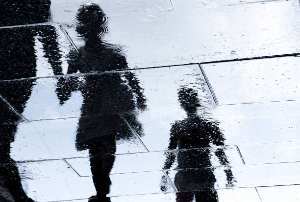 Blurry reflection silhouette of  people walking wet city street