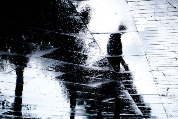Blurry reflection  silhouettes of  a man walking on a rainy day