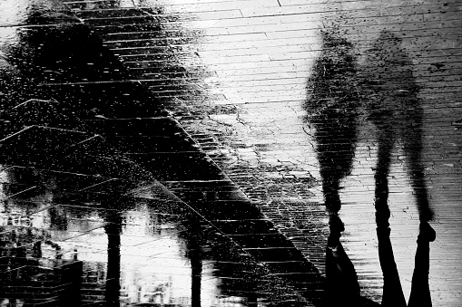 Blurry people shadow silhouette reflection on wet city sidewalk on a rainy day