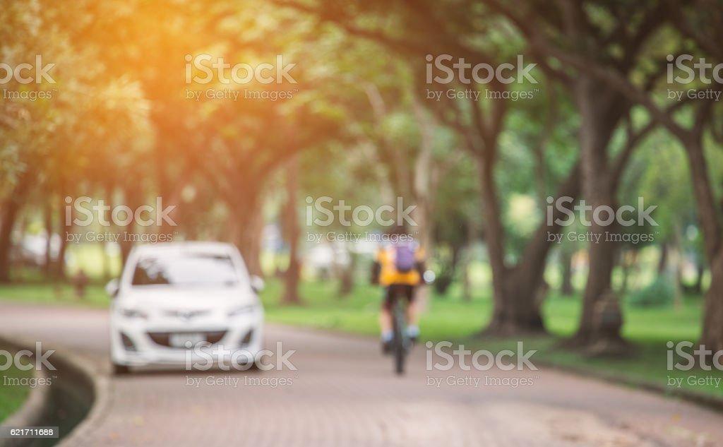 Blurry scene of biker passed white car in public park stock photo