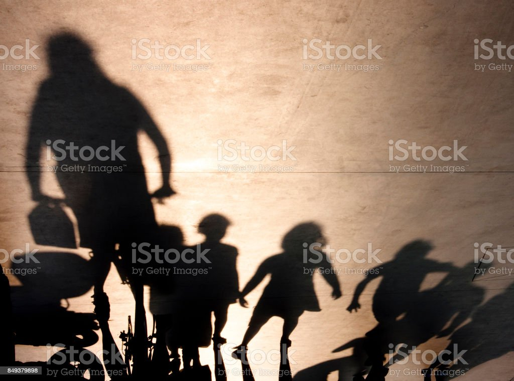Blurry shadow of a grown up person and a bunch of kids stock photo
