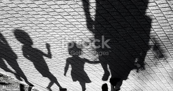 istock Blurry shadow of a little boy and a girl walking with adults 841222318