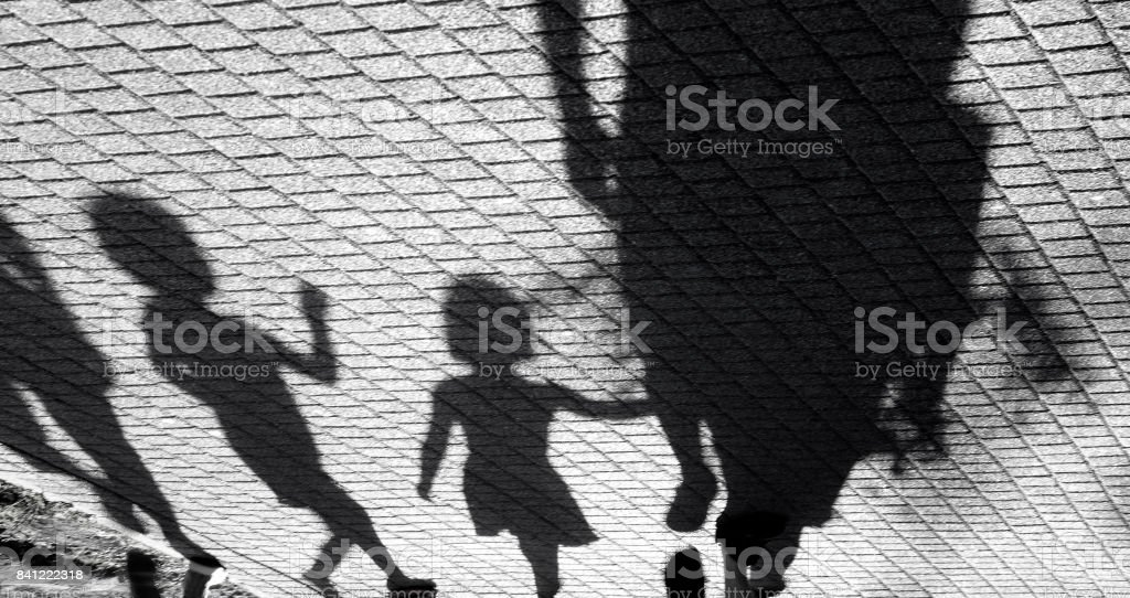 Blurry shadow of a little boy and a girl walking with adults stock photo