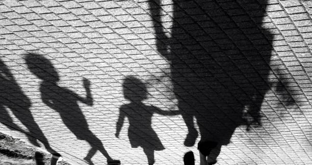 blurry shadow of a little boy and a girl walking with adults - criança perdida imagens e fotografias de stock