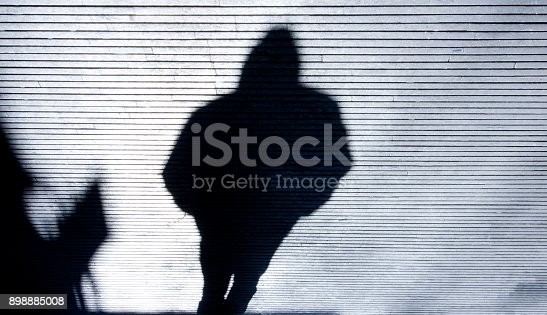 istock Blurry shadow of a person walking 898885008