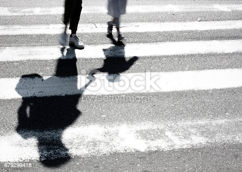Blurry shadow and silhouette of mother and child at zebra crossing