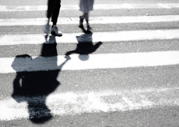 sombra embaçada de mãe e filho a atravessar a rua - vida de estudante - fotografias e filmes do acervo