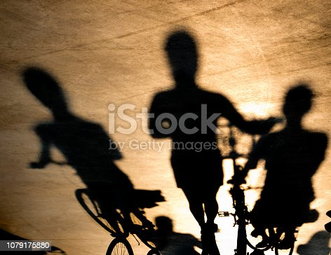 812812808 istock photo Blurry shadow of three young women on bikes 1079175880