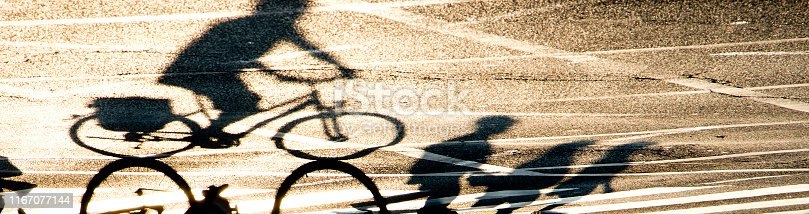 812812808 istock photo Blurry shadow silhouette of a  person riding a bike and pedestrians crossing the street with road markings 1167077144