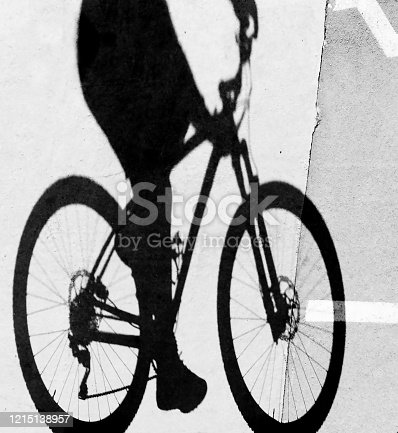 812812808 istock photo Blurry shadow silhouette of a young woman riding bicycle, detail 1215138957
