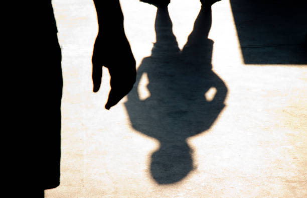 Blurry shadow silhouette of two boys confronting each other stock photo