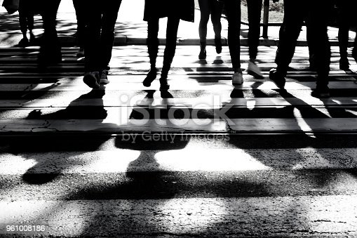 Blurry silhouettes and shadows of people crossing the street on crosswalk in black and white, only legs , unrecognizable